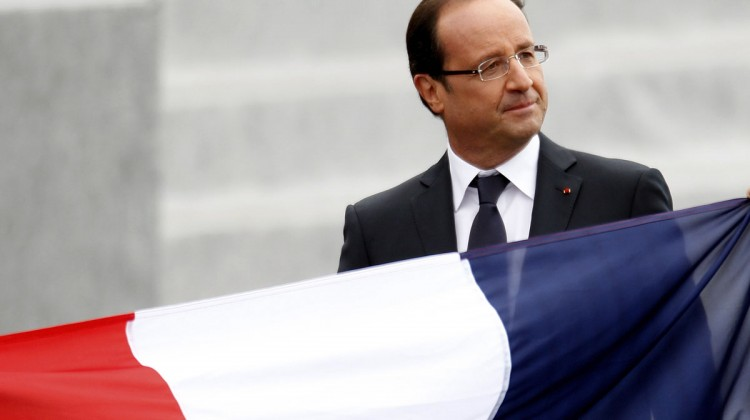 France's President Francois Hollande walks past a French national flag as he leaves the Place de la Concorde after the traditional Bastille Day military parade in Paris July 14, 2012. REUTERS/Charles Platiau (FRANCE - Tags: POLITICS MILITARY ANNIVERSARY) ORG XMIT: CHP05