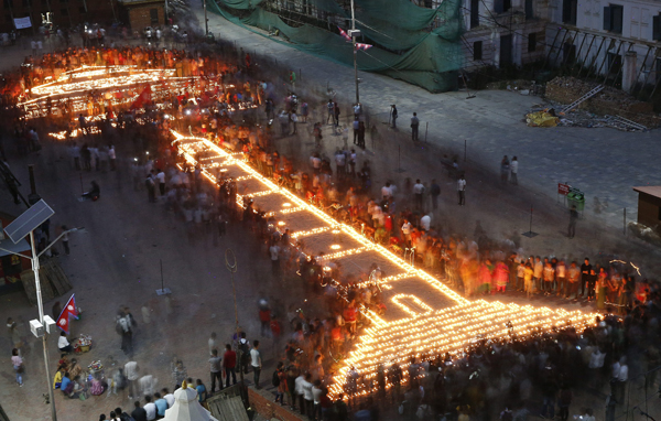 . Kathmandu (Nepal), 24/04/2016.- Nepalese gather to attend candle light vigil over an art of Dharhara Tower and Kasthamandap temple to mark the one year anniversary of devastating earthquake in Kathmandu, Nepal, 24 April 2016. The iconic Dharahara Tower and Kasthmandap temple collapsed during an earthquake. The citizens of Nepal are marking the one year anniversary of the quake that left over 8,000 people dead and more than 21,000 injured on 25 April 2015. (Protestas, Terremoto/sismo) EFE/EPA/NARENDRA SHRESTHA