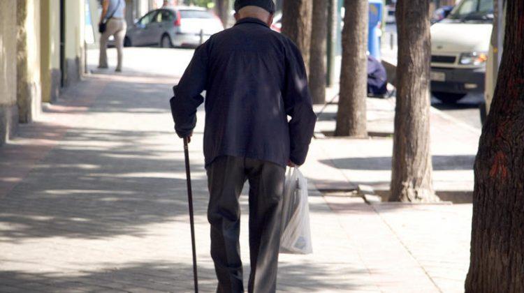Un se–or mayor pasea por una calle de Madrid.