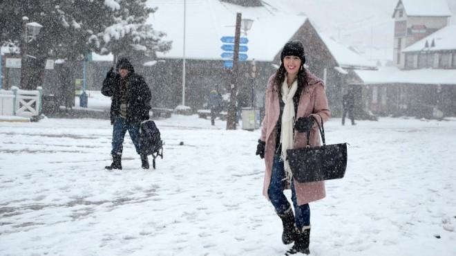 Una turista brasileñapasea por  la base del cerro Catedral, donde nieva intensamente
