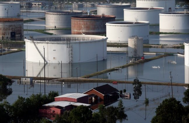 Holding tanks for a chemical company sit next to a home in floodwaters caused Tropical Storm Harvey in Port Arthur, Texas, Friday, Sept. 1, 2017. Port Arthur's major roads were swamped by rising waters brought by Harvey(AP Photo/LM Otero) (AP Photo/LM Otero)